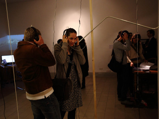 Visitors listening to audio tracks from the work 'NGO CIty' by Hieslmair/Zinganel.